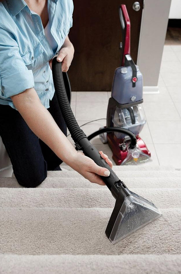 woman using carpet scrubbing machine on stairs